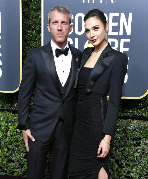 Jaron Varsano e Gal Gadot no tapete vermelho do Globo de Ouro, vestindo preto.